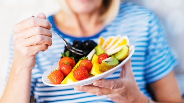 Woman holding a plate of fruit in one hand and a fork in the other hand
