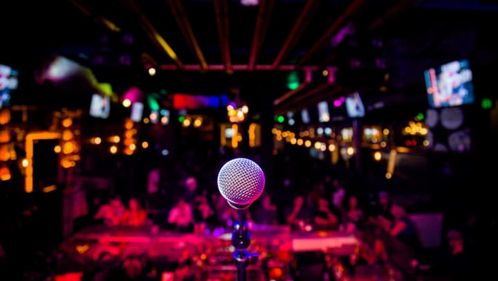 Point of view of a person on a stage. A mic is in the foreground. A dark, expansive nightclub is in the background.