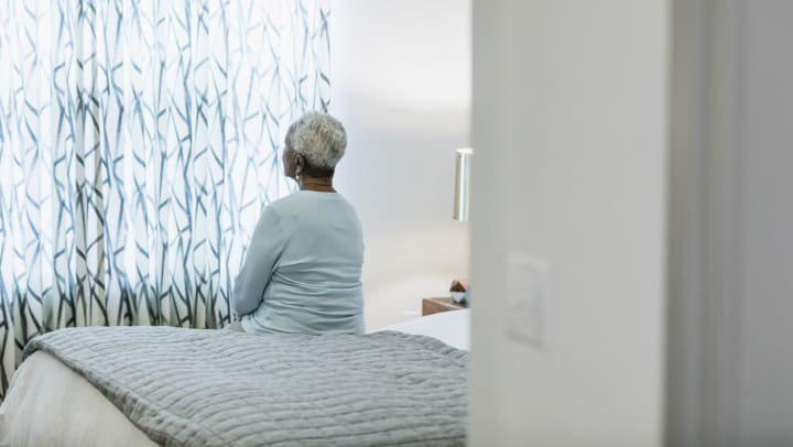Elderly woman sitting on a bed and looking out a window covered by drawn floral curtains.