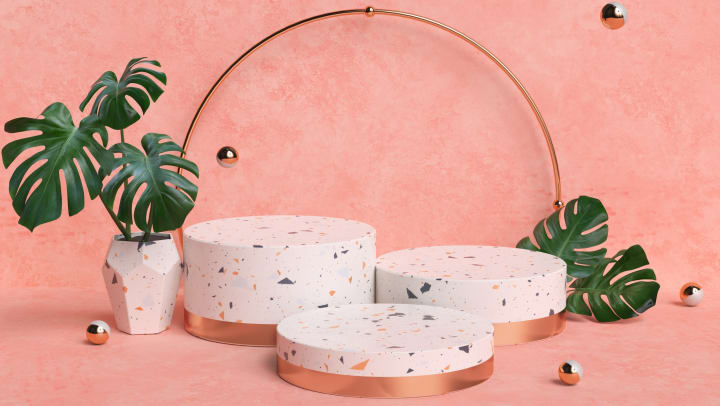 Terrazzo pot and plant stands in front of a pink wall.