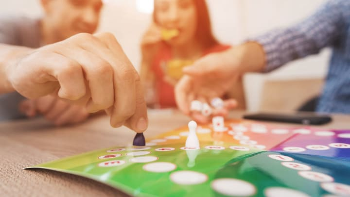 Young adults play a board game using dice and player tokens.
