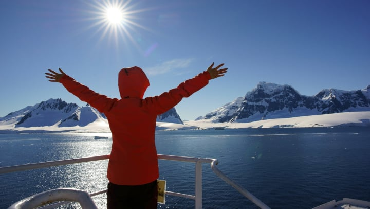 Woman on a ship with her hands up and back to the camera, snow covered mountains in front of her.