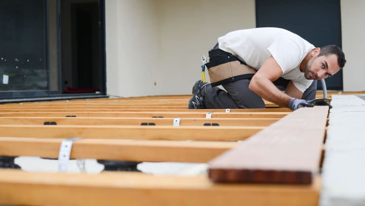 Man on his knees, working on a deck.