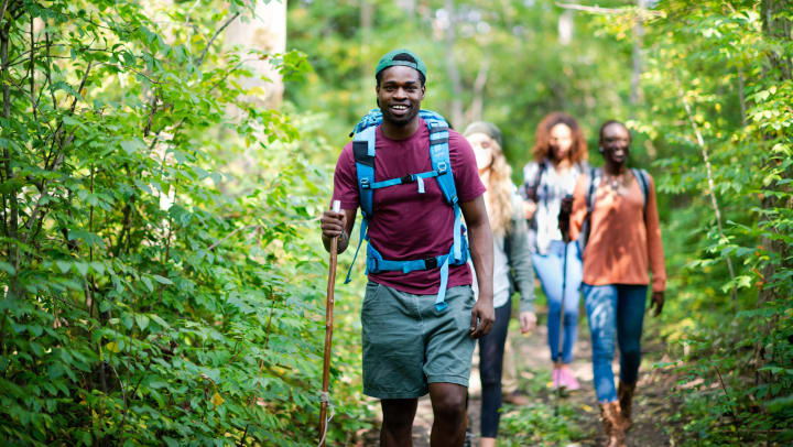 A diverse group of young adults hike through a trail in the woods on a sunny day.