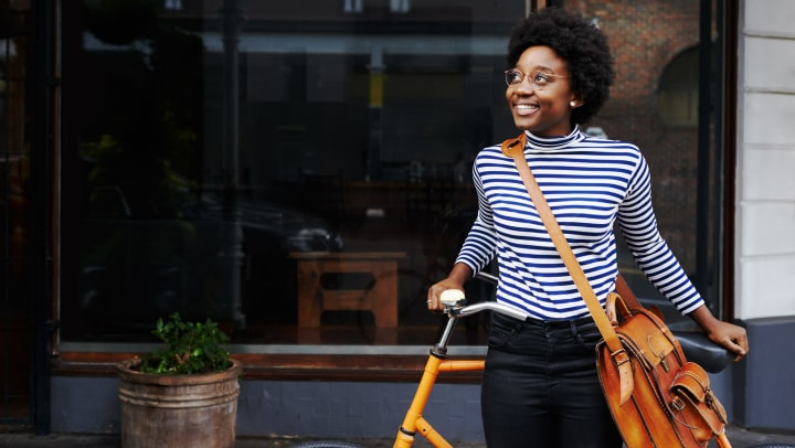 A smiling young woman leaning against a yellow bike in front of a shop window.