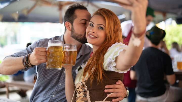 A young couple dressed in traditional German clothing and holding steins of beer, take a selfie.