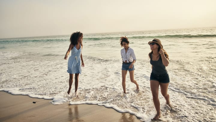 Three young women stand in ankle-deep waves at the beach.