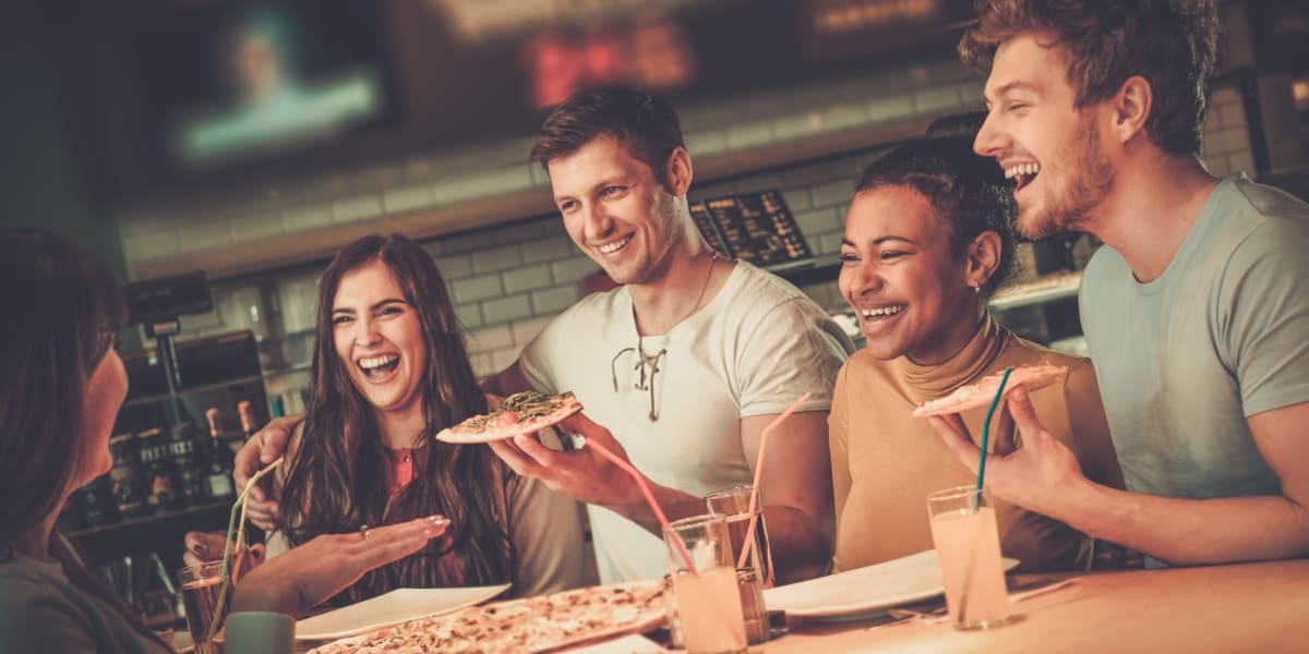 Friends eating pizza near Marquis Grand Lakes in Richmond, Texas