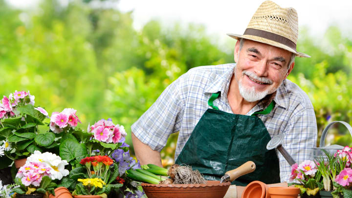 elderly man smiling with flower pots in front of him