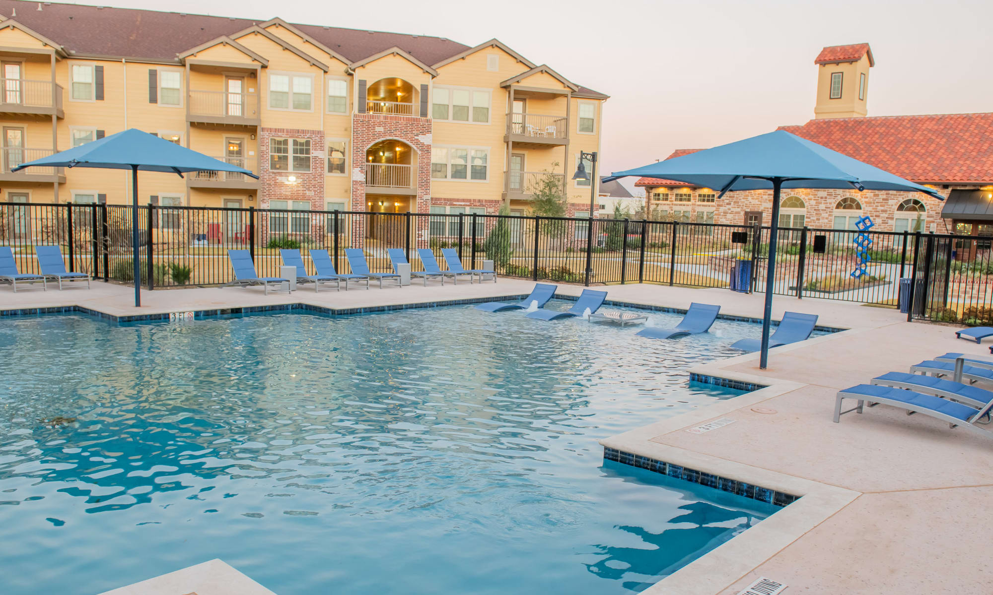 Outdoor resort style pool and exterior apartment view Portico at Friars Creek Apartments in Temple, Texas