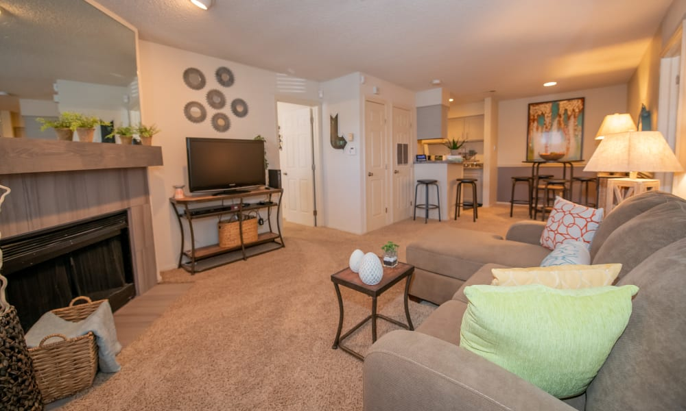 Bright living room with fireplace at Polo Run Apartments in Tulsa, Oklahoma