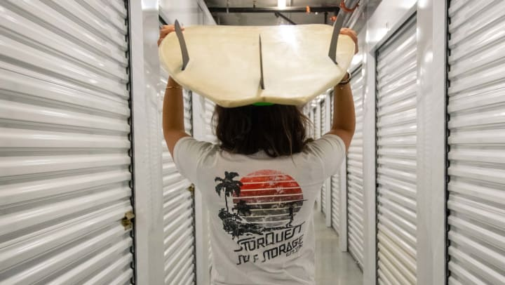 Person walks through a self storage corridor while holding a surfboard