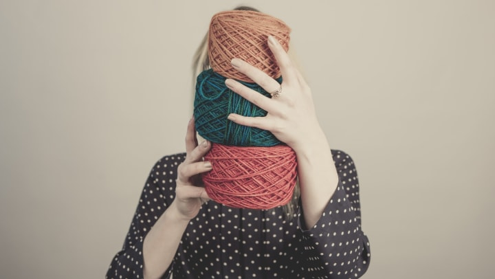 Woman holding 3 spools of colored yarn in front of her face at Mosaic Dallas