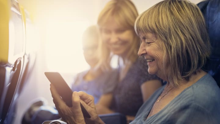 Older woman with cellphone and two other women on airplane.