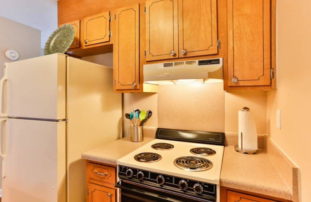 Kitchen with wood-style cabinets at Huntersville Apartment Homes in Huntersville, North Carolina