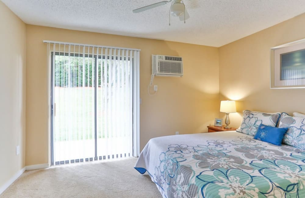 Bedroom with back patio access at Huntersville Apartment Homes in Huntersville, North Carolina
