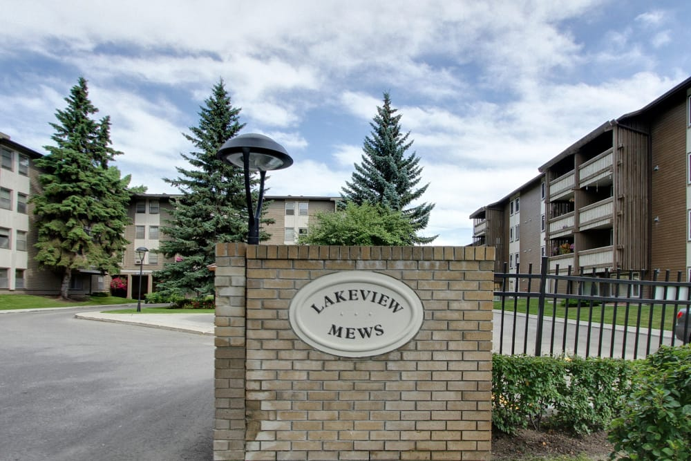 Driveway entrance with sign at Lakeview Mews in Calgary, Alberta
