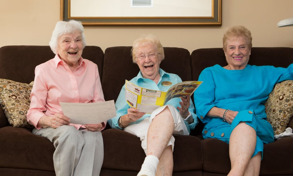 Smiling residents on a couch together at The Keystones of Cedar Rapids in Cedar Rapids, Iowa