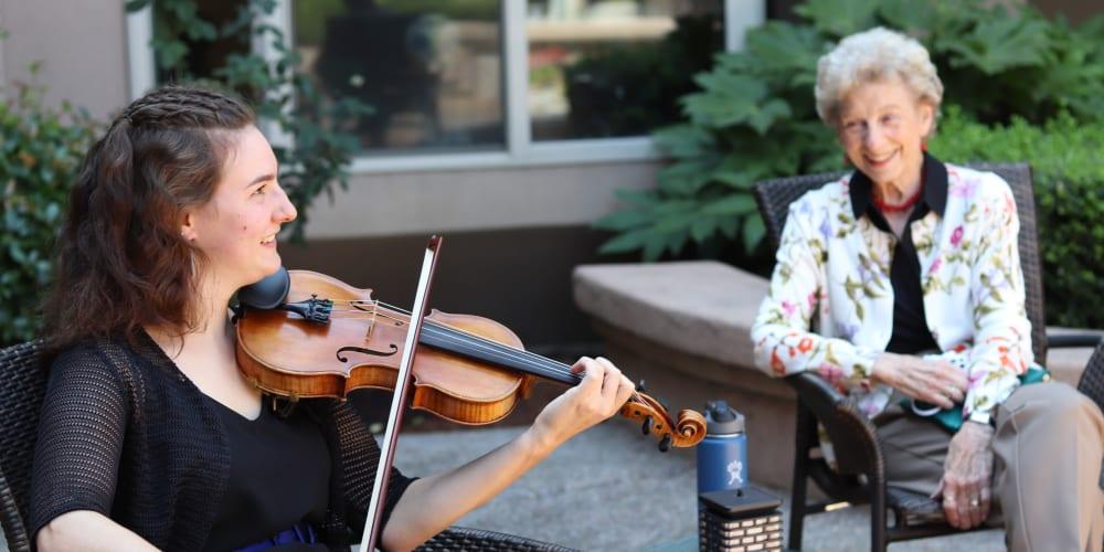 Resident enjoying violin music at The Springs at Anna Maria in Medford, Oregon