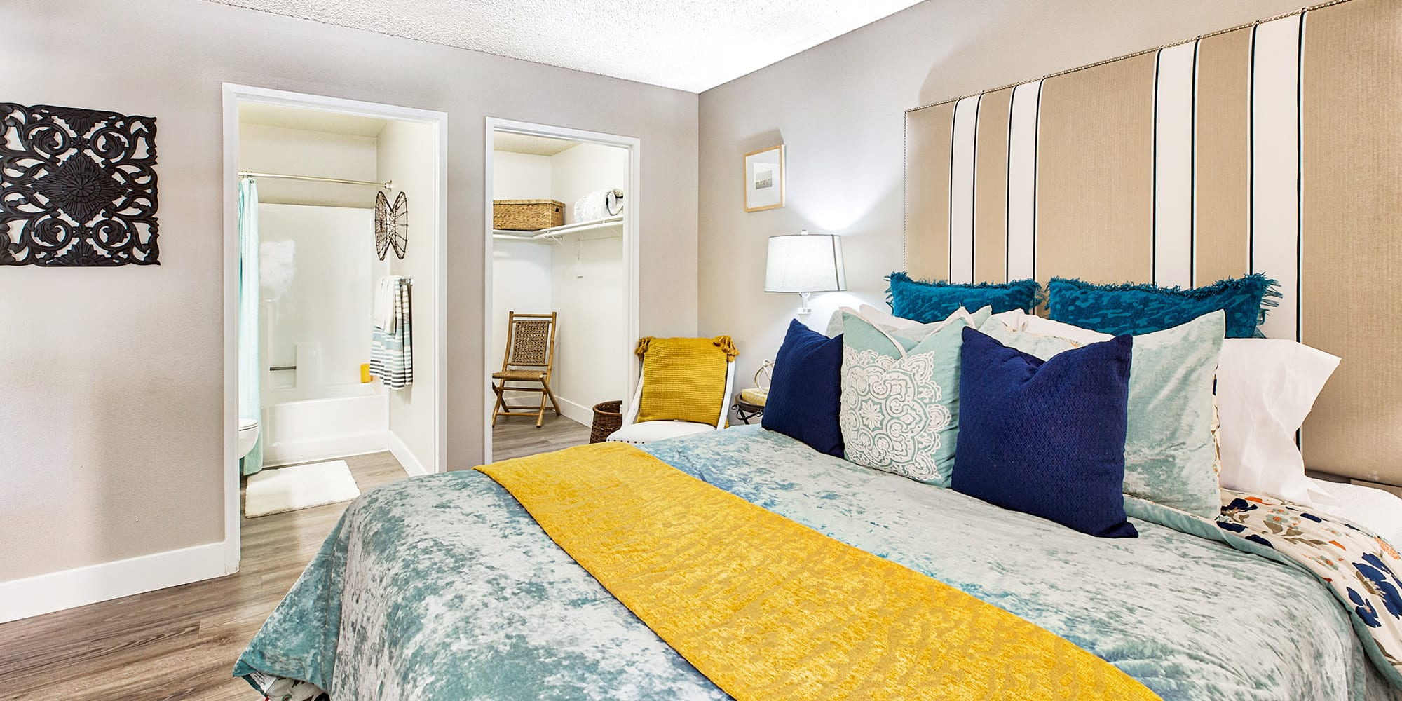Modern furnishings in a model home's primary bedroom with an en suite bathroom and walk-in closet at Mountain Vista in Victorville, California