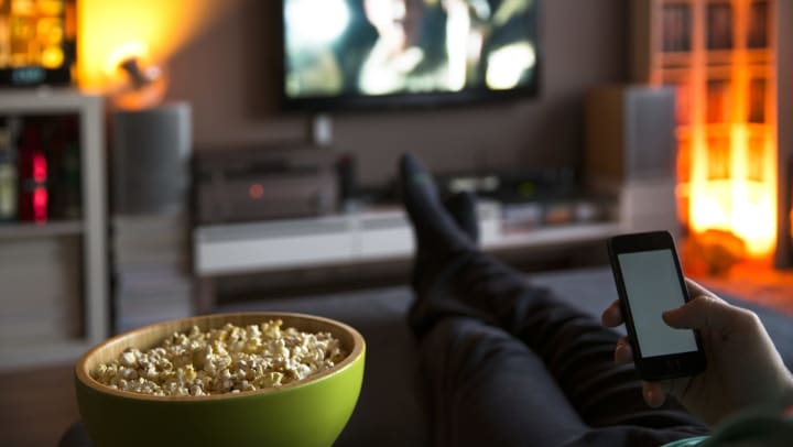 A bowl of popcorn in the foreground. A person on their phone, we only see their hand holding a cellphone, and crossed legs. In the background is a television.