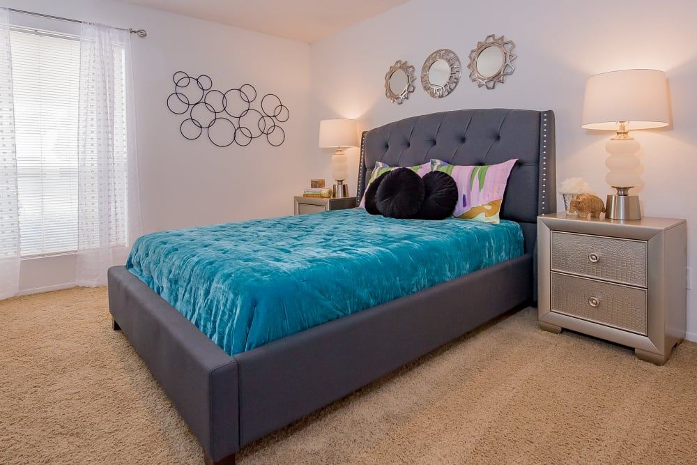 Model bedroom with bed and dresser at Windsail Apartments in Tulsa, Oklahoma