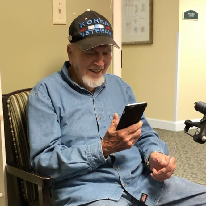 Resident facetiming family at Grand Villa of Pinellas Park in Pinellas Park, Florida