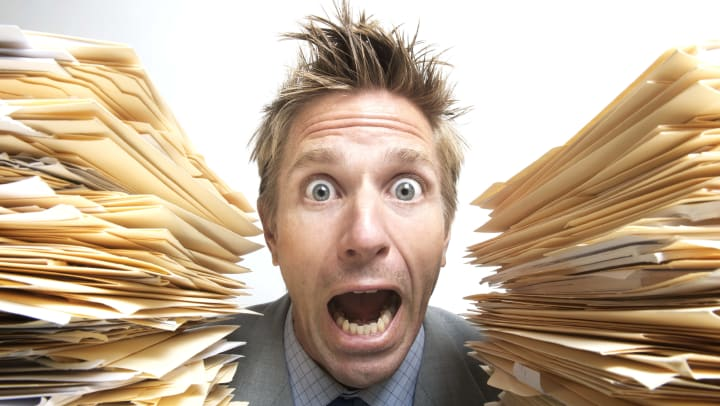 A stressed-looking man screams for help between two tall, messy stacks of file folders.