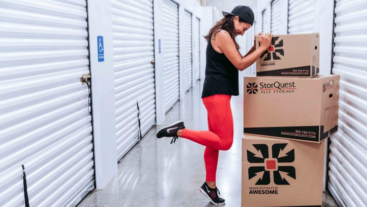 A woman balancing against storage boxes inside a self storage facility hallway