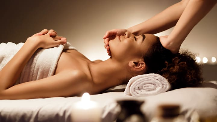 Smiling woman wrapped in a towel, lying on a massage table with hands touching her head and face.