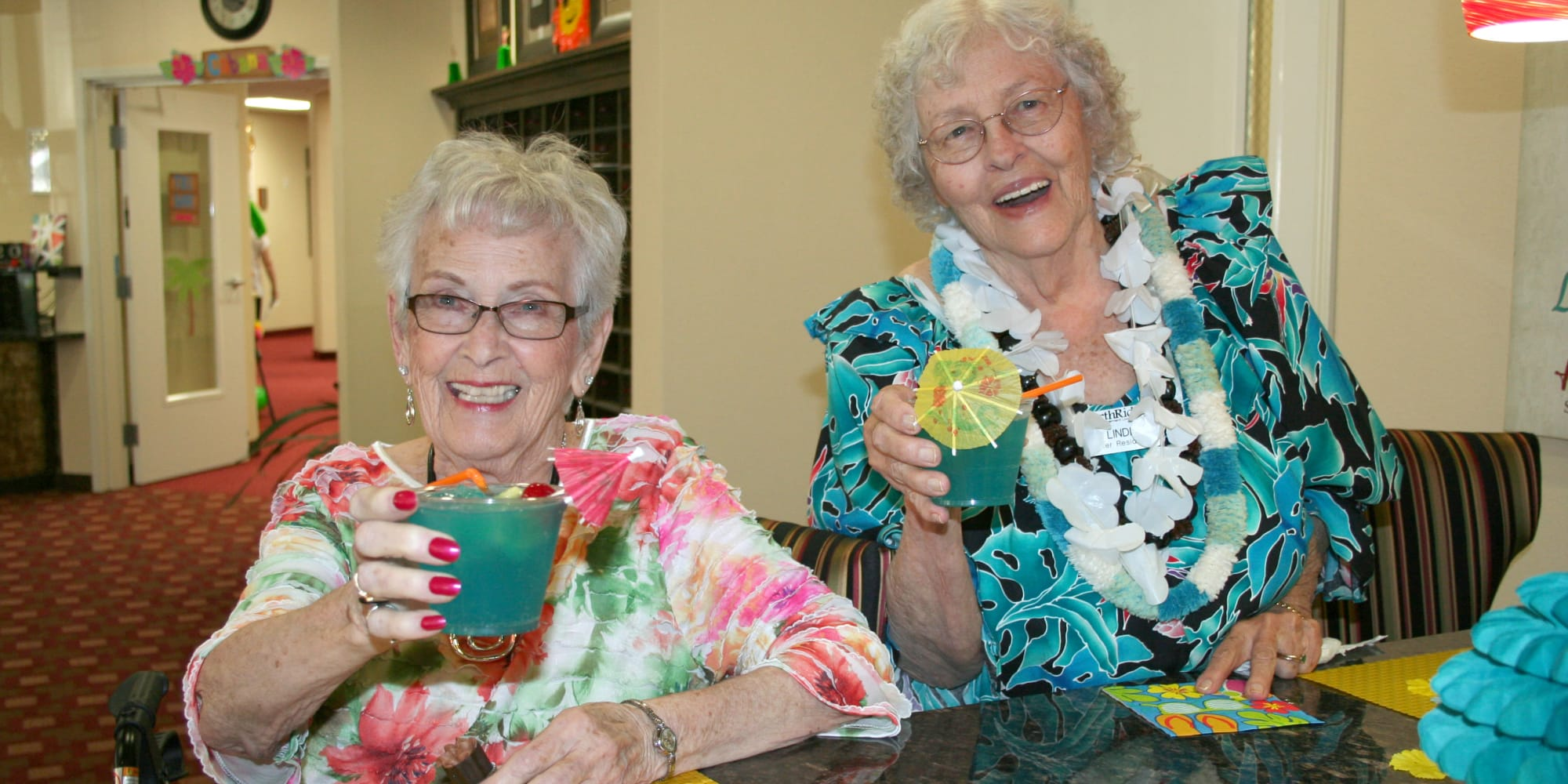 Two residents from Ashwood Meadows Gracious Retirement Living in Johns Creek, Georgia, with drinks