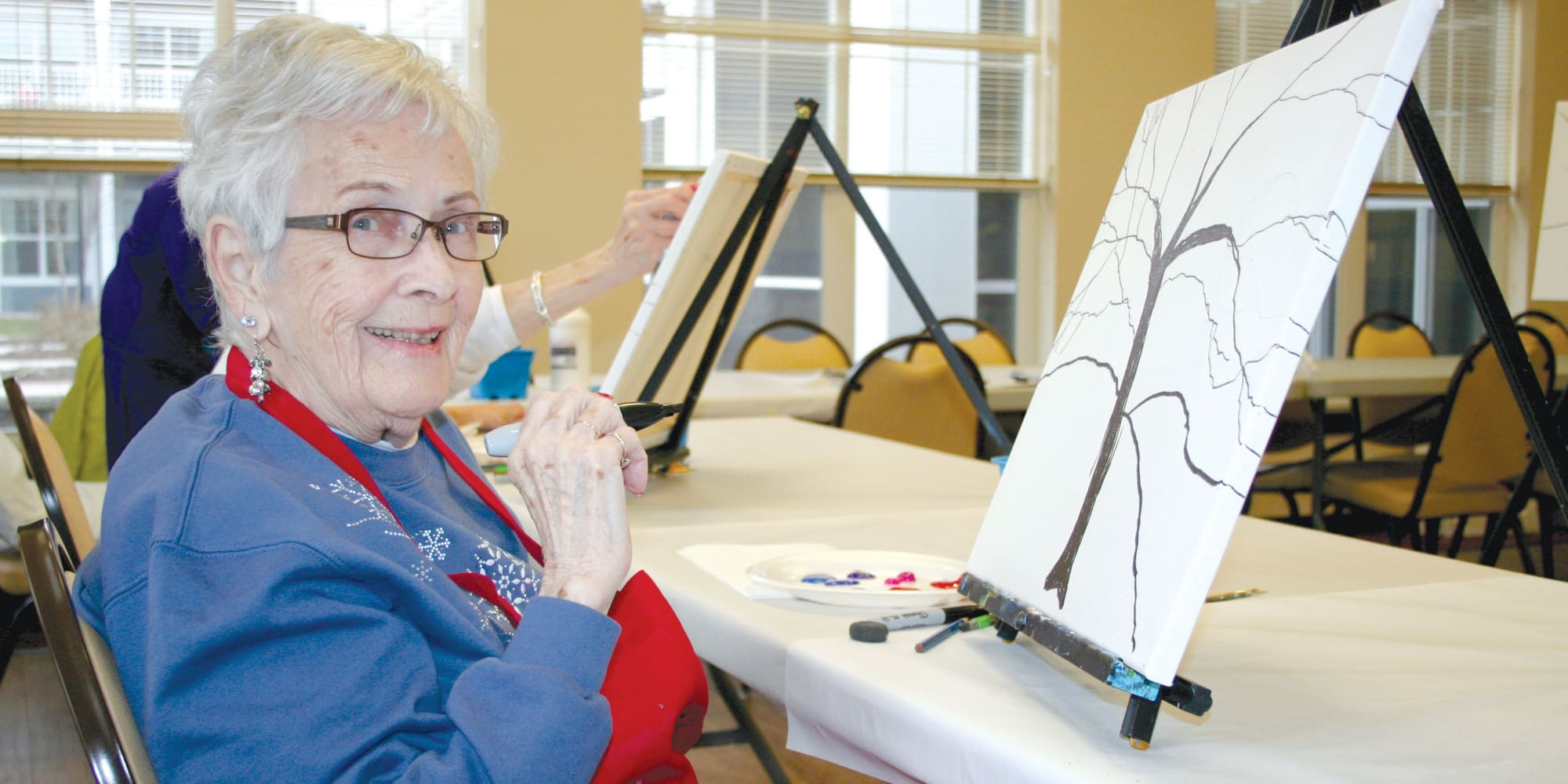 A resident painting a tree at Cypress Springs Gracious Retirement Living in Bradenton, Florida