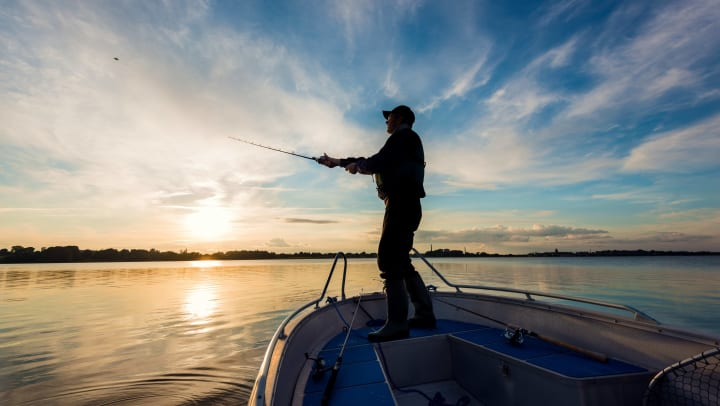 Angler standing atop a boat casts a fishing line into the water