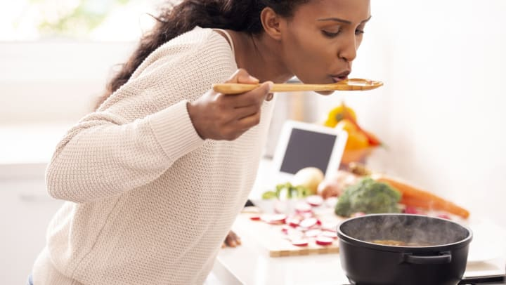 A woman tastes the soup that is simmering on her stove. Chopped vegetables sit on the counter in the background.