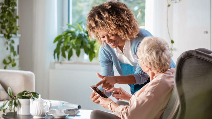 A young woman smiling and pointing at a smartphone while standing next to a seated older woman
