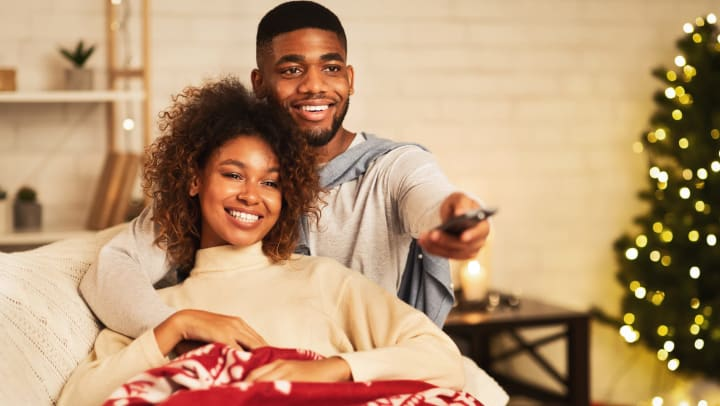 Couple sitting on couch with Christmas blanket watching movies