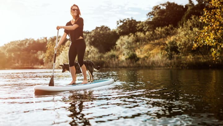A smiling woman enjoys a peaceful moment on the water with her dog on a paddle board.
