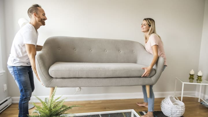 A smiling man and woman placing a sofa in their living room