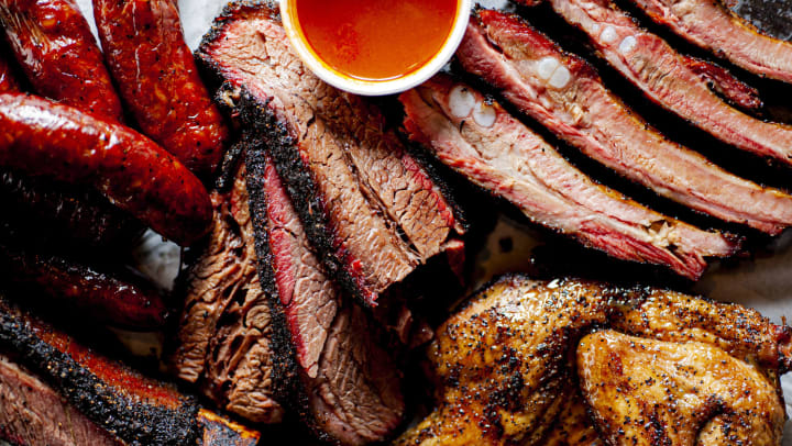 A variety of barbecued meats on parchment paper including brisket, smoked chicken, ribs, and sausage with a cup of sauce.
