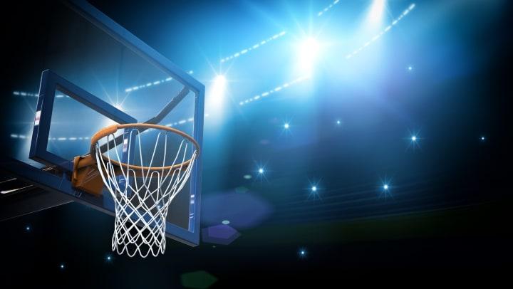 A basketball hoop under bright lights.