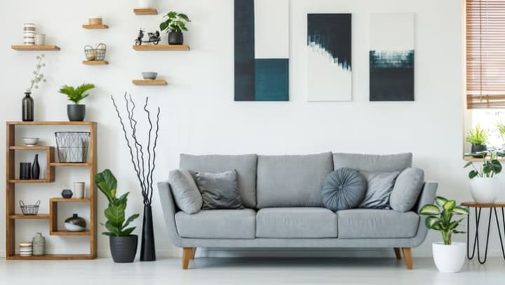 Elegant living room interior with a comfy couch, paintings and shelves at {{location_name}} in {{location_city}}, {{location_state_name}}