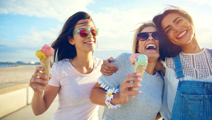 Laughing girls enjoying ice cream cone near {{location_name}}