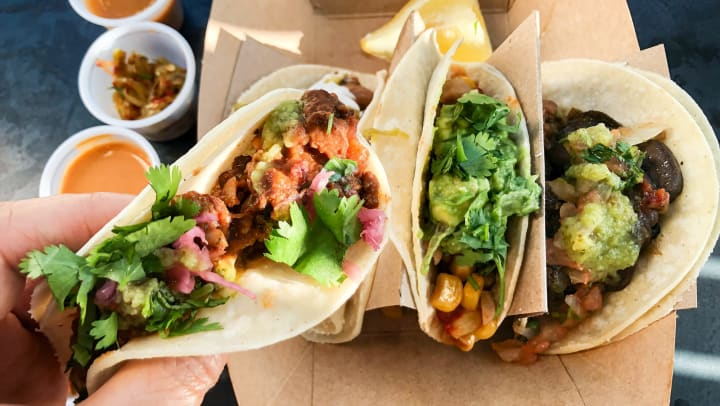 A hand holding tacos filled with beans, mushrooms, corn, guacamole, and pico de gallo.