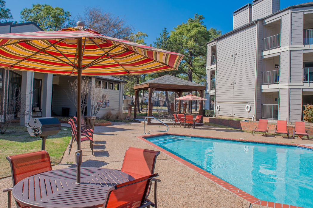 Covered seating by the pool at Woodscape Apartments in Oklahoma City, Oklahoma