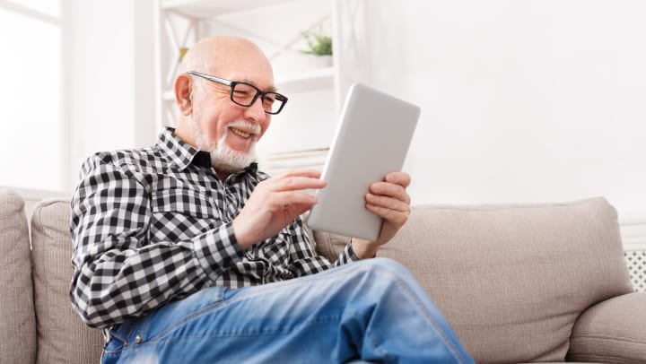 Senior man reading tablet