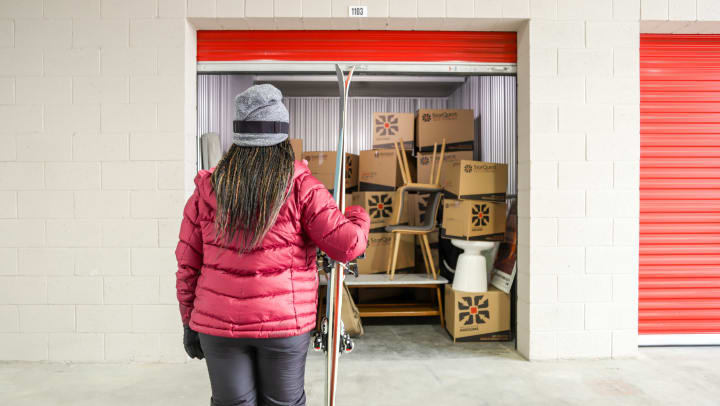 Woman holding skis with back to camera looking into a storage unit full of boxes