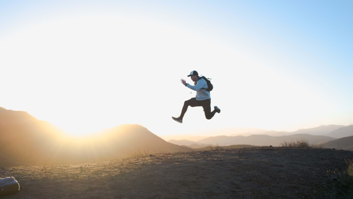 A man jumping in the air with the sun rising behind him.