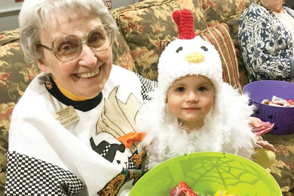 A resident with a child in a costume at Meadowlark Estates Gracious Retirement Living in Lawrence, Kansas