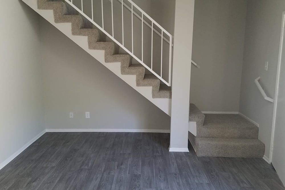 Hardwood floors leading to plush carpet on the upper floor staircase in model home at Sienna Heights Apartment Homes in Lancaster, California