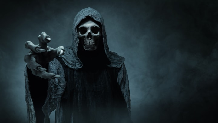 The grim reaper reaches towards the camera.